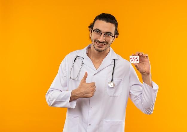 Sorridente giovane medico con occhiali medicali che indossa abito medico con lo stetoscopio tenendo le pillole il pollice in alto su giallo