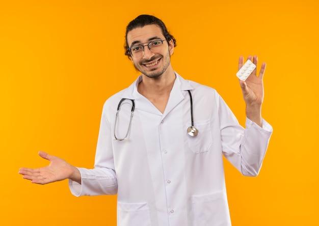 Sorridente giovane medico con occhiali medicali indossando abito medico con stetoscopio tenendo pillole e punti con mano a lato su giallo