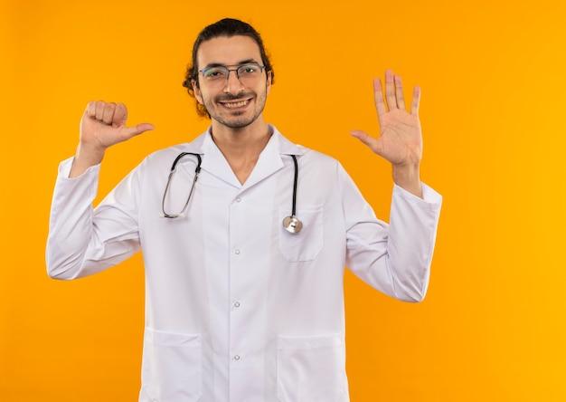 Sorridente giovane medico con occhiali medicali che indossa una veste medica con uno stetoscopio che mostra diversi gesti su giallo