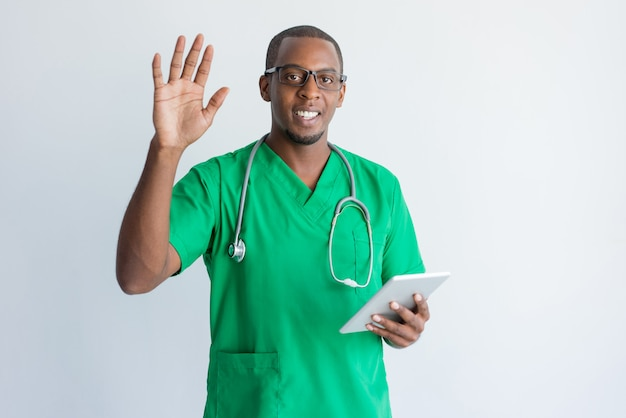 Smiling young doctor with touchpad waving hand.