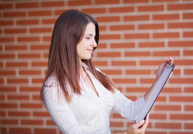 Smiling young elegant businesswoman with clipboard standing in a bright office