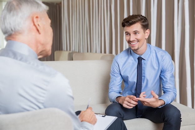 Smiling young employee talking to business leader