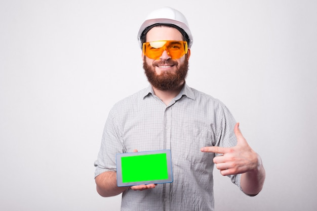 Smiling young engineer pointing at green screen on tablet and wearing white helmet
