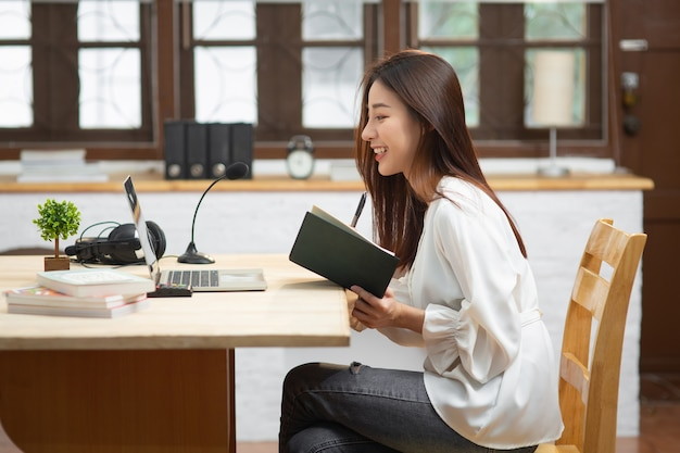 Smiling young entrepreneur asian business woman working with internet using computer sit at apartment