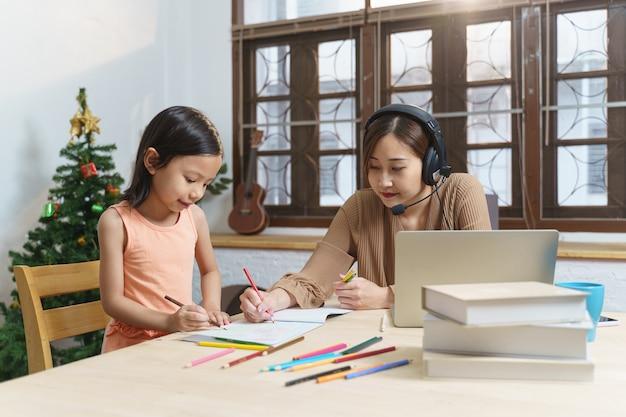 웃고 있는 젊은 기업가 아시아 여성 사업가가 노트북을 사용하여 인터넷 작업을 하는 동안 집 사무실에 앉아 있는 동안 그녀의 딸이 숙제를 하고 원격 온라인 교육을 홈스쿨링으로 학습합니다.