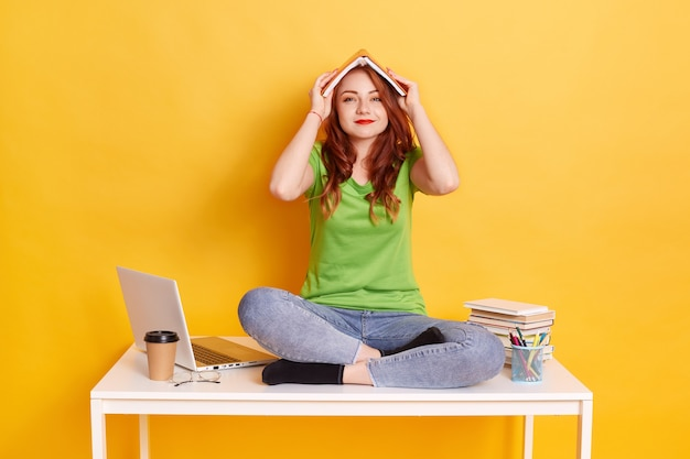 足を組んでテーブルに座って、頭の上に本を置いて屋根を作る若いヨーロッパ人女性の笑顔、カメラを見て、カジュアルに身に着けて、本、ラップトップ、コーヒーで囲みます。