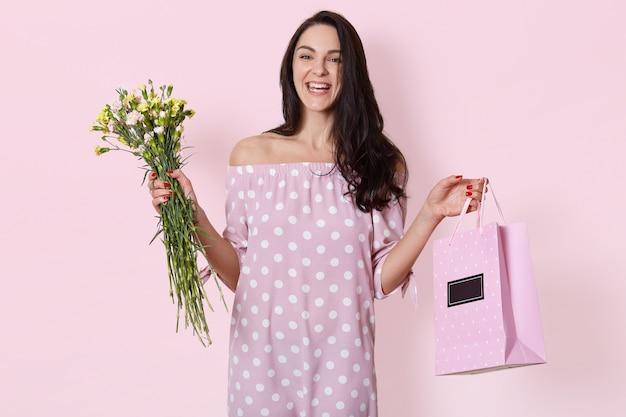 Улыбающаяся молодая европейская женщина с темными длинными волнистыми волосами, одетая в розовое платье в горошек, держит подарочную сумку и букет цветов, позирует на светло-розовом, имеет день рождения.