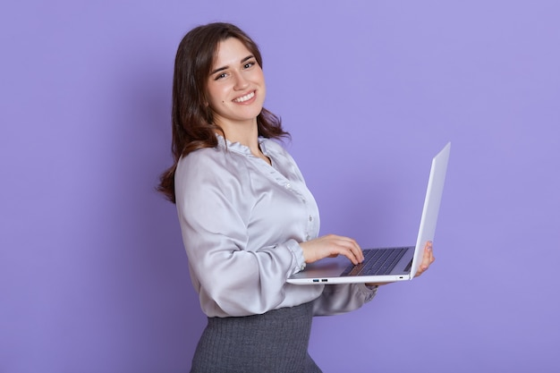 Smiling young european woman wearing elegant clothing posing isolated on lilac wall, holding and working on laptop pc computer, with happy expression.