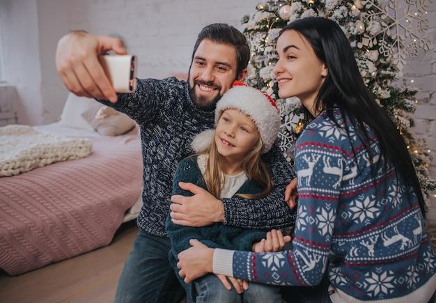 Улыбается молодая семья в рождественской атмосфере, делая фото с помощью смартфона.
