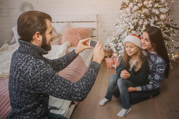 スマートフォンで写真を作るクリスマスの雰囲気の中で若い家族の笑顔。