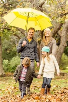 傘の下で若い家族を笑顔