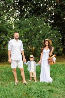 夏の日の週末を楽しみながら、幼い息子と一緒に立っている若い父と母の笑顔。家族とレジャーのコンセプト