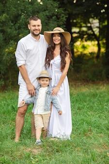 夏の日の週末を楽しみながら、幼い息子と一緒に立っている若い父親と母親の笑顔。家族やレジャーのコンセプト