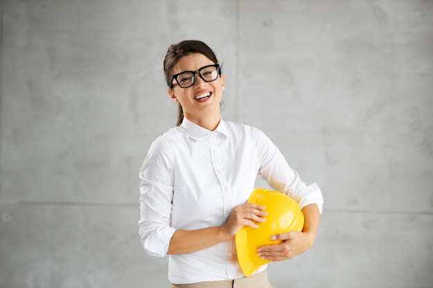Smiling young female architect standing with helmet in her arms and looking at camera.