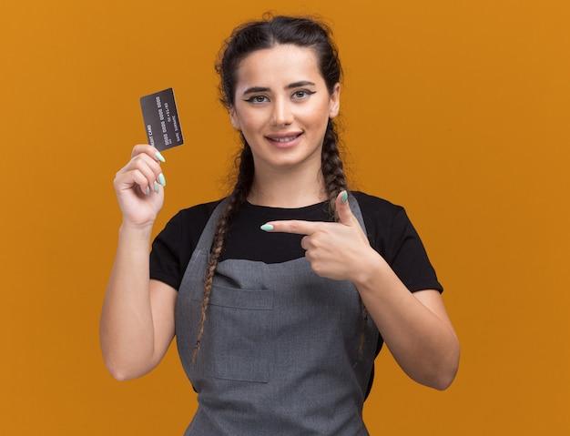 Улыбающаяся молодая женщина-парикмахер в униформе держит и указывает на кредитную карту, изолированную на оранжевой стене