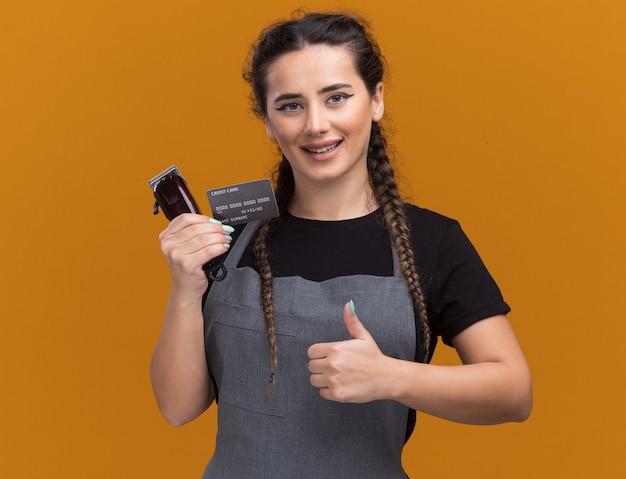 オレンジ色の壁に分離された親指を示すクレジットカードとバリカンを保持している制服を着た若い女性の理髪師の笑顔