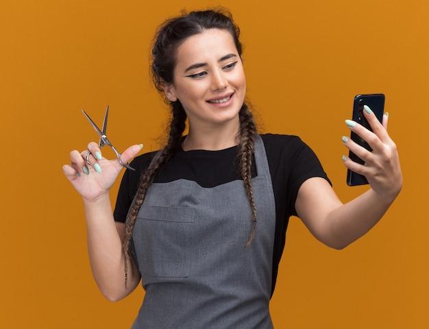 はさみを保持し、オレンジ色の壁に隔離された彼女の手で電話を見て制服を着た若い女性の床屋の笑顔