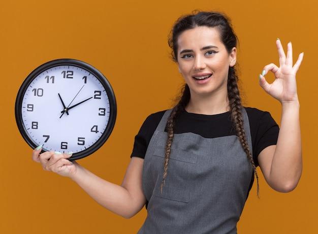 Sorridente giovane donna barbiere in uniforme che tiene l'orologio da parete che mostra il gesto giusto isolato sulla parete arancione