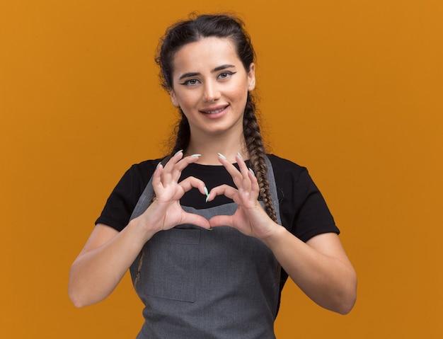 Sorridente giovane barbiere femminile in uniforme che mostra il gesto del cuore isolato sulla parete arancione