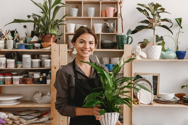 Smiling young female ceramist holding plant.