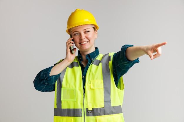 Улыбающаяся молодая женщина-строитель в защитном шлеме и защитном жилете разговаривает по телефону, глядя и указывая в сторону