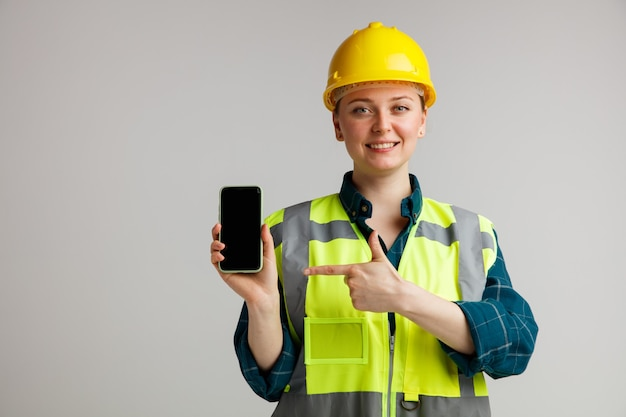 Smiling young female construction worker wearing safety helmet and safety vest holding and pointing at mobile phone
