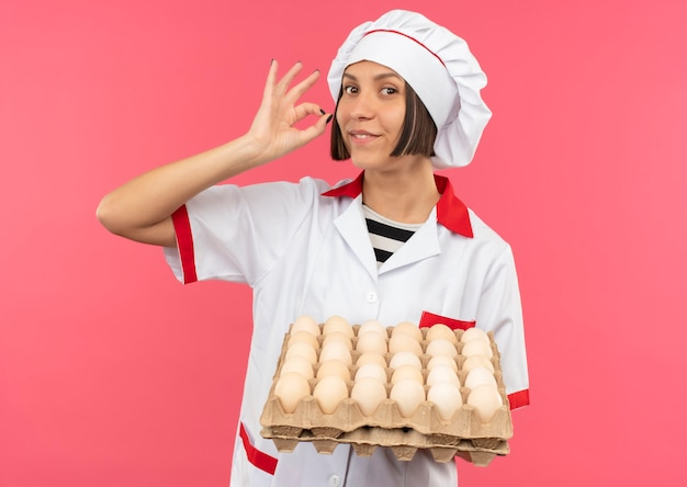 Smiling young female cook in chef uniform holding carton of eggs and doing ok sign isolated on pink wall