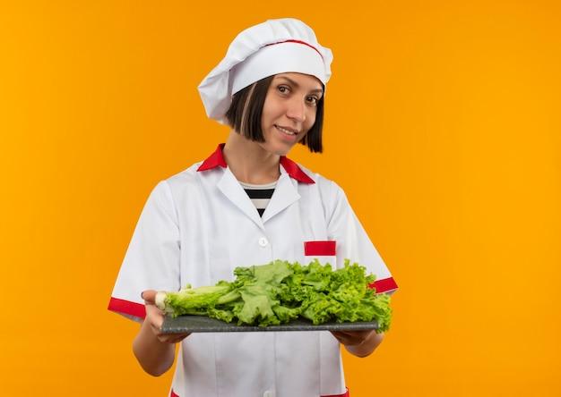 Sorridente giovane cuoco femminile in uniforme del cuoco unico che tiene tagliere con lattuga su di esso isolato sulla parete arancione