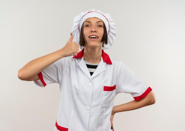Sorridente giovane donna cuoca in uniforme da chef mettendo la mano sulla vita e mostrando il pollice in alto isolato sul muro bianco