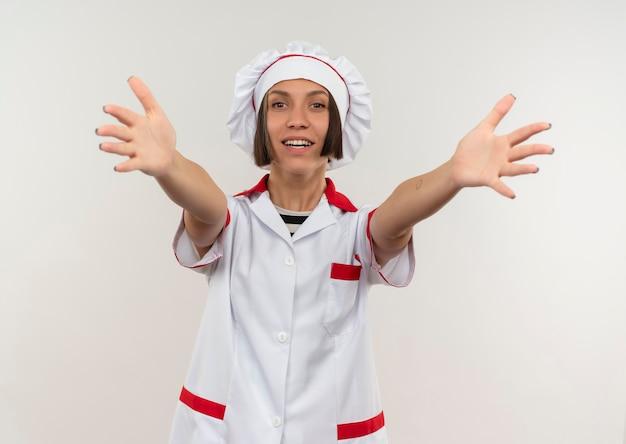 Sorridente giovane donna cuoco in uniforme del cuoco unico che allunga le mani verso la parte anteriore isolata sulla parete bianca