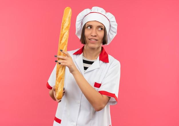 분홍색 벽에 고립 된 측면을보고 빵 막대기를 들고 요리사 유니폼에 웃는 젊은 여성 요리사