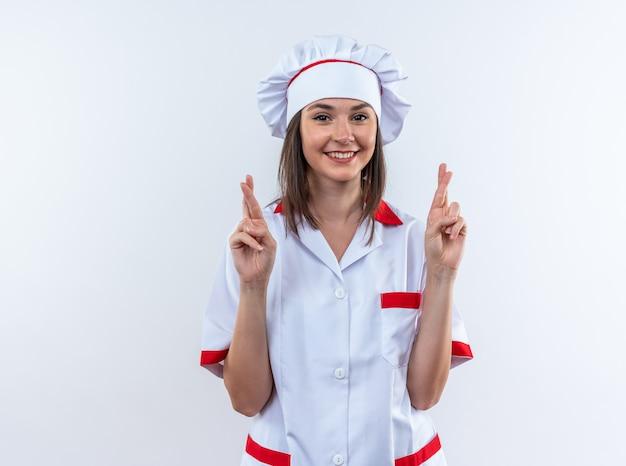 Улыбающаяся молодая женщина-повар в униформе шеф-повара, скрестив пальцы, изолирована на белой стене
