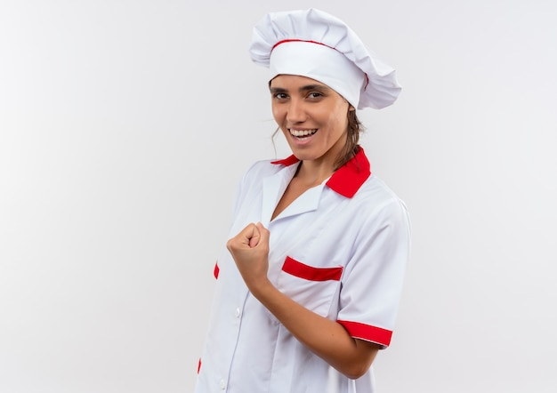 Smiling young female cook wearing chef uniform doing strong gesture with copy space