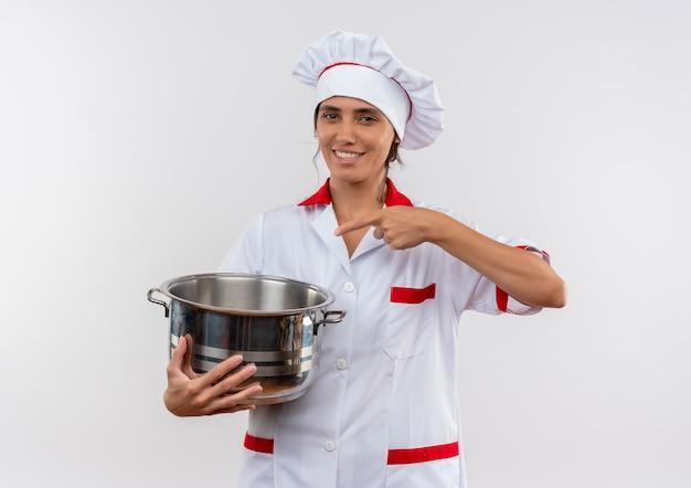 笑顔の若い女性料理人がシェフの制服を着て、コピースペースのある鍋を指しています