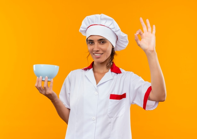Улыбающаяся молодая женщина-повар в униформе шеф-повара держит миску и показывает жест окей