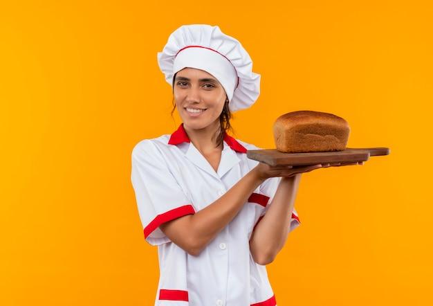 コピースペースとまな板にパンを保持しているシェフの制服を着て笑顔の若い女性料理人