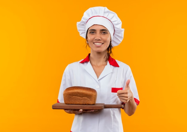 コピースペースで彼女の親指を切り刻む上でパンを保持しているシェフの制服を着て笑顔の若い女性料理人