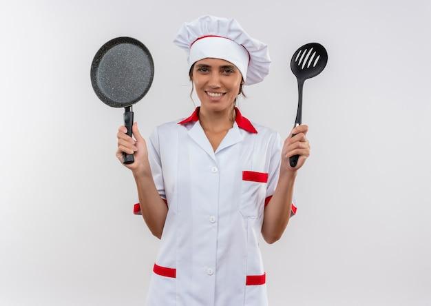 Sorridente giovane femmina cuoco indossando lo chef uniforme tenendo padella e spatola con copia spazio