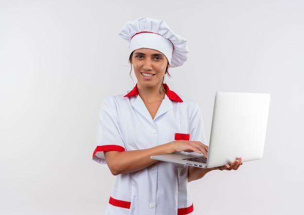 Улыбающаяся молодая женщина-повар в униформе шеф-повара держит ноутбук с копией пространства