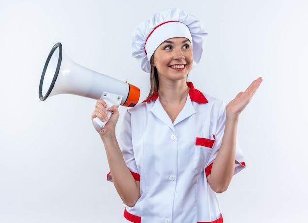 Улыбающаяся молодая женщина-повар в униформе шеф-повара держит громкоговоритель на белом фоне