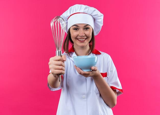 ピンクの背景に分離されたカメラで泡立て器でボウルを差し出すシェフの制服を着て笑顔の若い女性料理人 無料写真