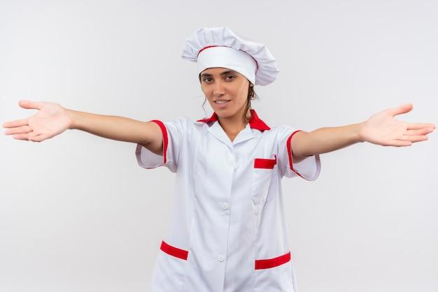 Sorridente giovane femmina cuoco indossando lo chef uniforme tendendo le mani alla telecamera