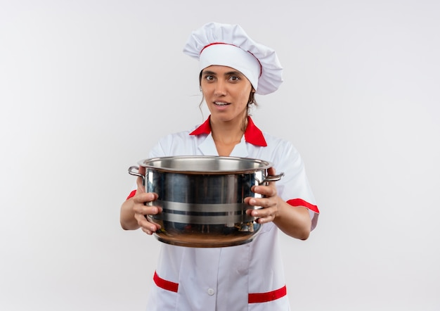 Smiling young female cook wearing chef uniform holding out saucepan to camera with copy space
