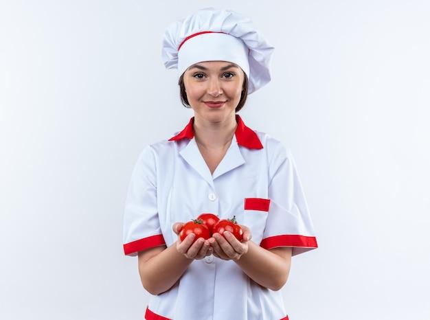흰색 배경에 고립 된 카메라에서 토마토를 들고 요리사 유니폼을 입고 웃는 젊은 여성 요리사