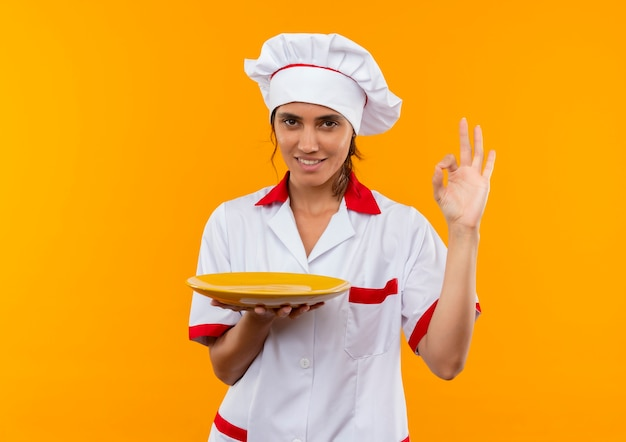 Улыбающаяся молодая женщина-повар в униформе шеф-повара держит тарелку и показывает жест окей с копией пространства