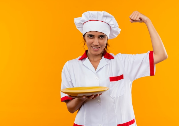 Smiling young female cook wearing chef uniform holding plate and showing strong gesture  with copy space
