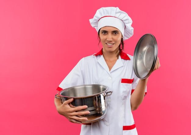Улыбающаяся молодая женщина-повар в униформе шеф-повара держит кастрюлю и крышку с копией пространства