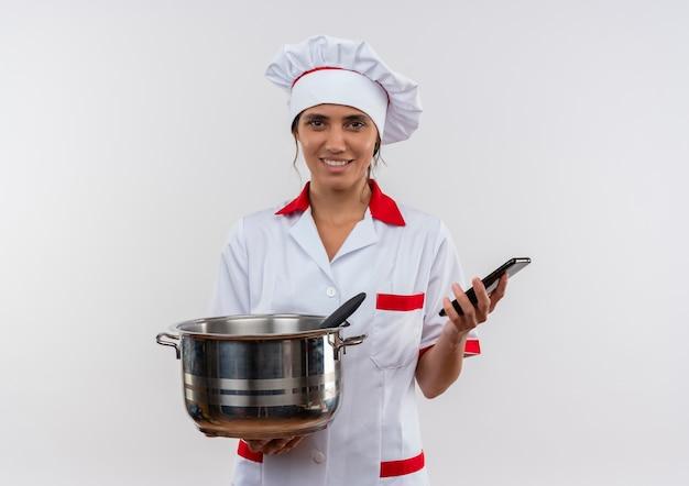 コピースペースと鍋と電話を保持しているシェフの制服を着て笑顔の若い女性料理人