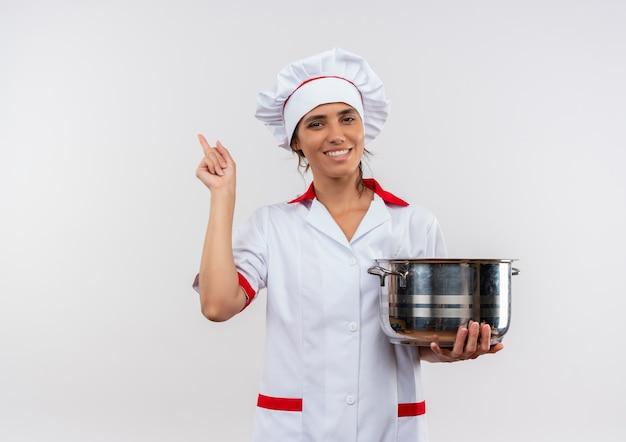 鍋を保持し、コピースペースで横を指すシェフの制服を着て笑顔の若い女性料理人