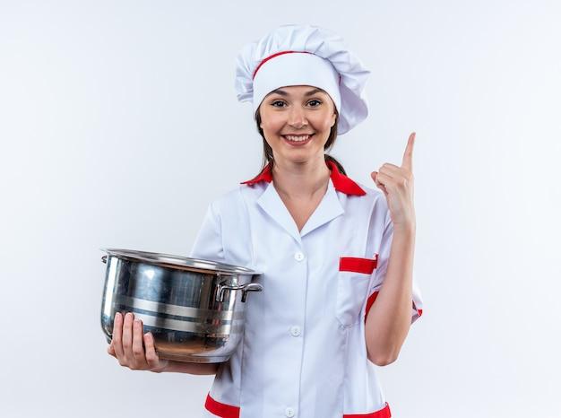 白い壁に隔離された上に鍋を指しているシェフの制服を着て笑顔の若い女性料理人
